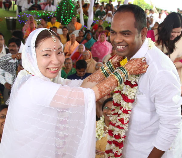 Asuka (left) puts a wedding garland on her husband Chaitanya (right) during their Hindu ceremony